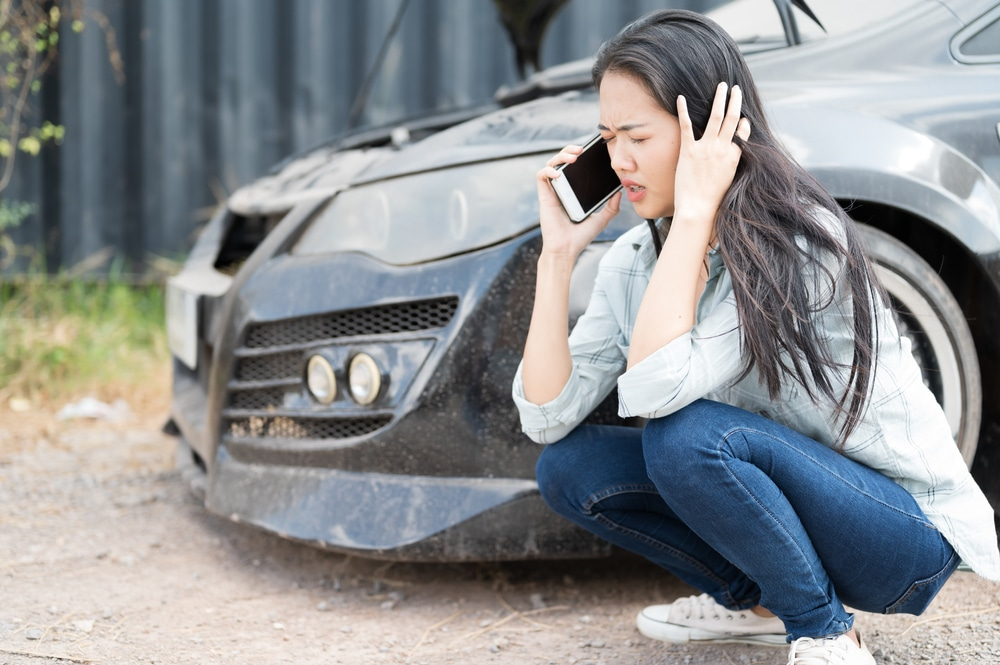 Woman talking on a cellphone while sitting next to a broken down car